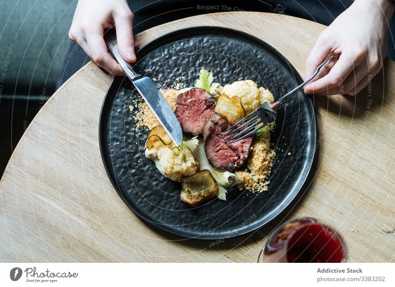 Person having roast beef with vegetables for meal chip dinner eat slice gastronomy cauliflower cutlery restaurant cream sauce garnish portion plate fresh