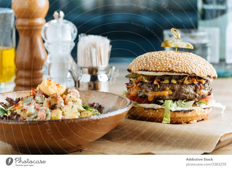 Classic burger and salad in restaurant dish cafe patty cutlet colorful vegetable sauce cheese modern bowl roast garnish rustic classic prepare appetizer fried