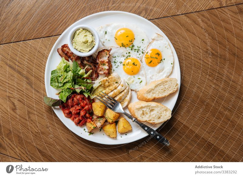 Delicious breakfast meal with fried eggs and veggies english toast bacon vegetable bean potato salad cuisine dish plate calorie guacamole modern morning