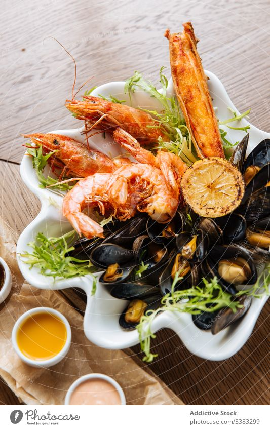 Seafood appetizer plate with assortment of sauces seafood prawn grill mussel delicacy culinary restaurant cafe delicious dish sweet chili sauce thousand island