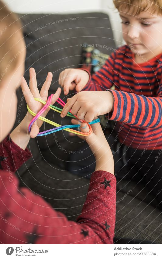 Smart children using rubber bands for game creative colorful learn upbringing kid play elastic together little palm twist casual home fun holiday rest relax