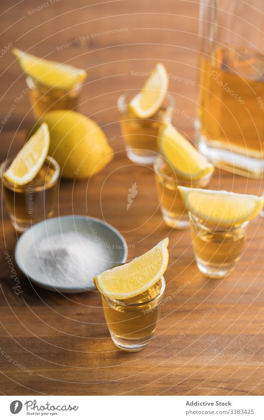 Tequila in shots with salt rim and lemon alcohol tequila booze table wooden glass beverage drink fresh tasty citrus orange party delicious yellow organic food
