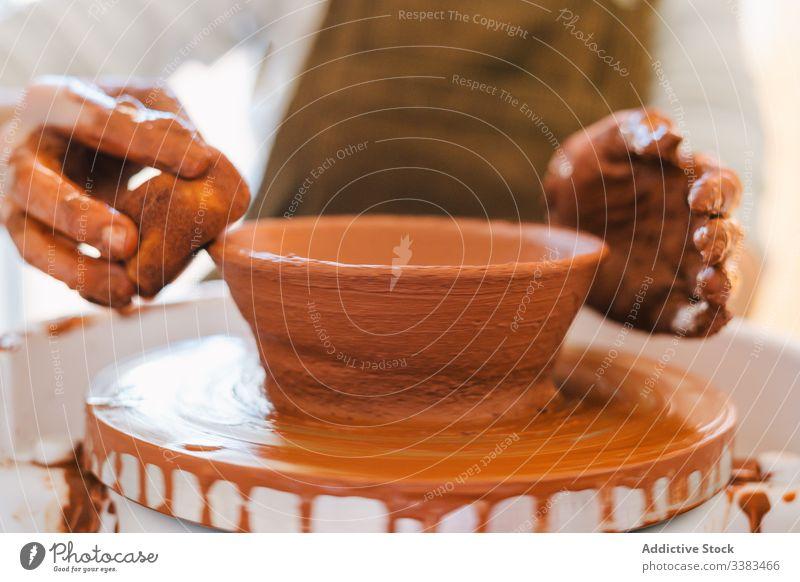 Artisan crafting earthenware in workshop artisan pottery handmade clay crockery circle person ceramic spin equipment master utensil jar creative professional