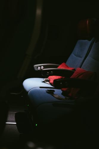 A row of seats in the plane with red cushions and seat belts in the dark Airplane Airplane seat Flying travel Tourism Cushion Night Dark somber Empty