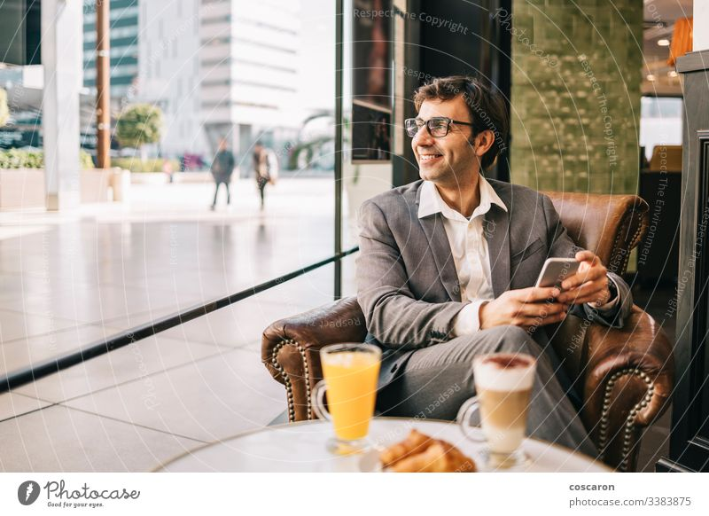 Businessman at the bar having a cup of coffee and orange juice adult application breakfast business businessman cafe cheerful communication drinking executive