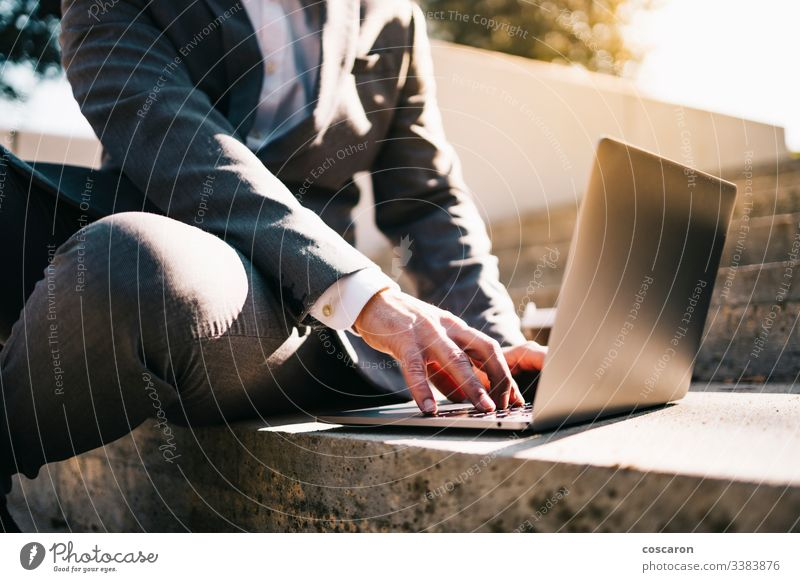 Smiling young business man sitting on steps with laptop and coffee. adult beard bearded businessman caucasian city computer concept connection employee