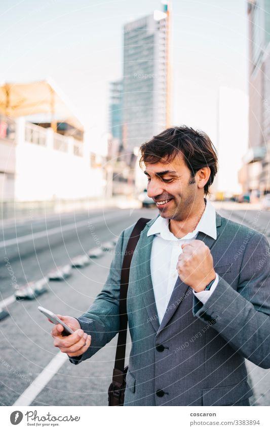 Handsome mature businessman celebrating victory achievement barcelona beard building businessperson cellphone cellular cheerful city communication concept