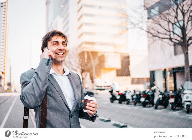 Smiling businessman talking by phone adult attractive barcelona blue building call calling cell cellphone cheerful city closeup communication confidence