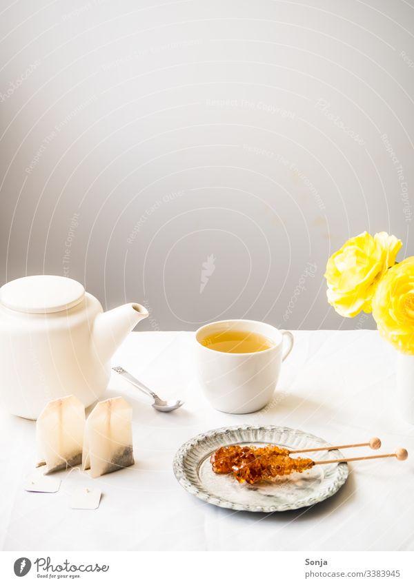 Teepause mit Kräutertee und Kandiszucker blume frühling kräutertee kandiszucker teepause teekanne wand weiß teebeutel löffel tasse heiß getränk süß tischtuch