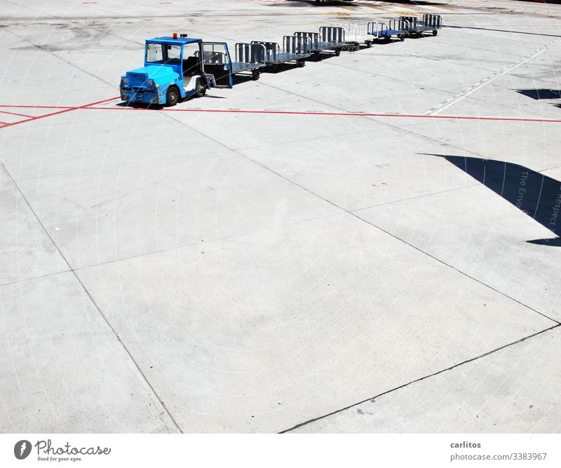 Baggage trolley without luggage at the airport at the parking position of a shadow-throwing aircraft Airport Luggage baggage car Transport Tractor Trailer