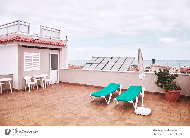 Rooftop with sunbeds on a cloudy day. summer city roof vacation relax retro sky lifestyle sunbathing deck chair clouds terrace view travel town architecture