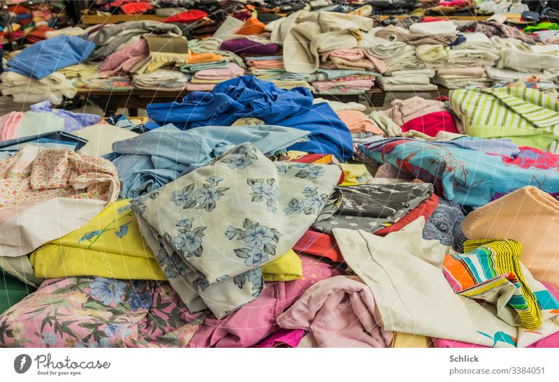 Rummage table and folded textiles in the background Bargain counter Textiles second hand Cloth Clothing Second-hand Second hand shop Muddled variegated Stack