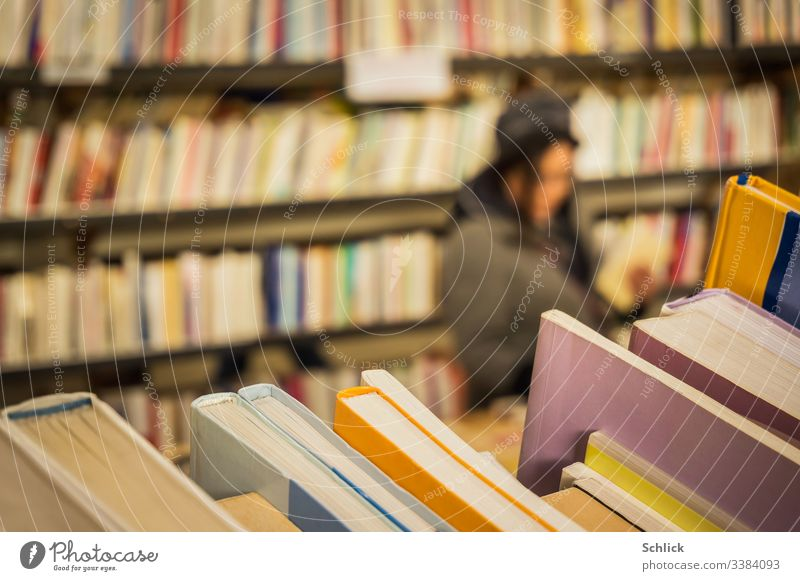 Close-up second hand books in a bookstore with a customer in blur Second-hand shop Woman selective focus bokeh Bookshelf Many Shallow depth of field Diagonal