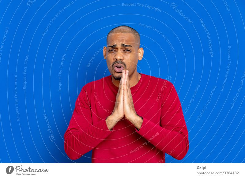 African guy with a red jersey black blue ask pray fist faith believer meditation christian catholic adult people person african male american man isolated