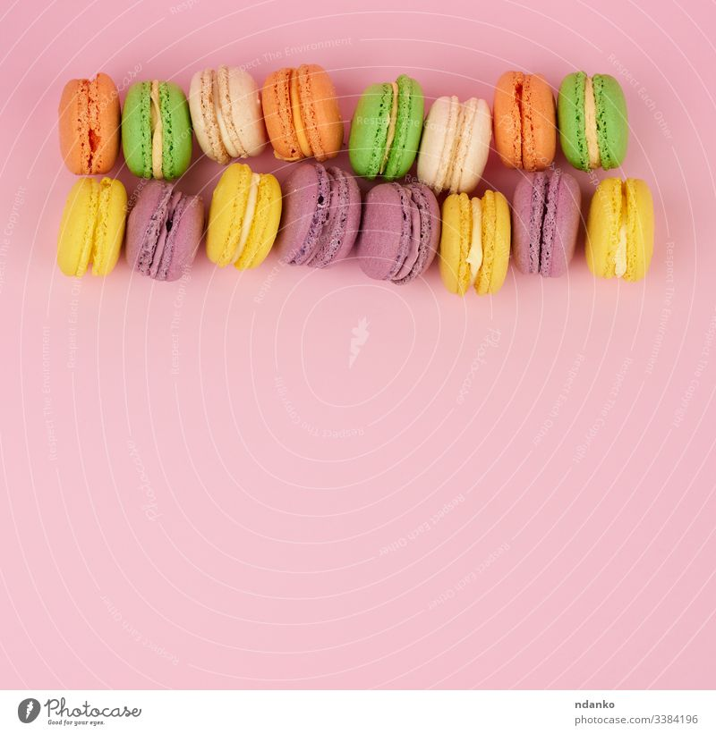 yellow, purple round baked macarons cakes on a pink background, dessert lies in a row macaroon meringue nobody pastry pile sandwich set snack stack sugar sweet