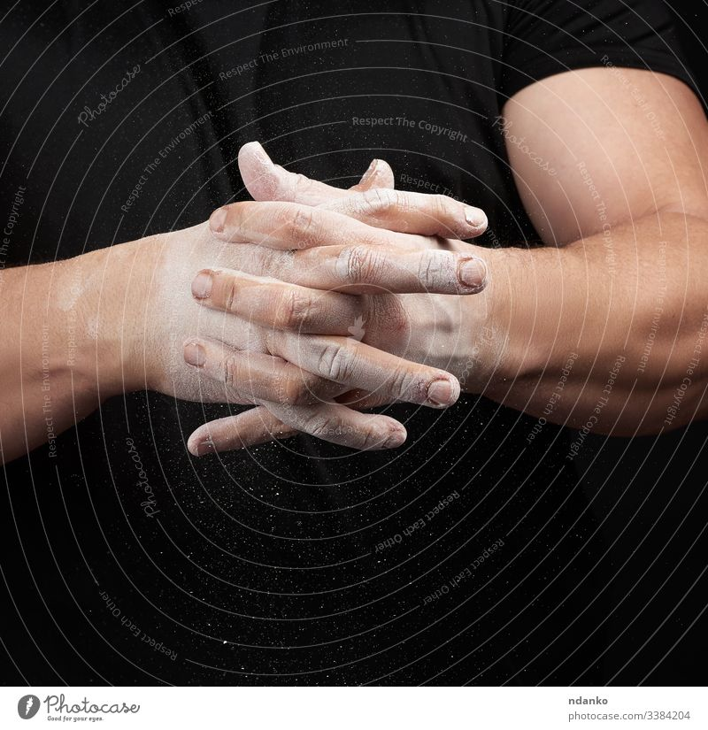 muscular athlete in a black uniform rubs his hands with white dry sports magnesia powder power preparing scattered sportsman sporty strength strong talc talcum