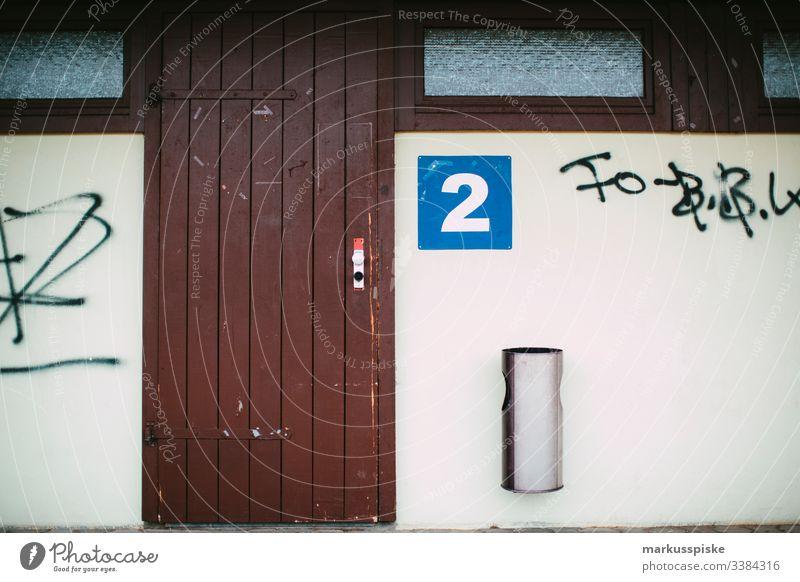 changing cubicle cabin Hut House (Residential Structure) Daub Graffiti number 2 litter bins Wooden door run-down Derelict