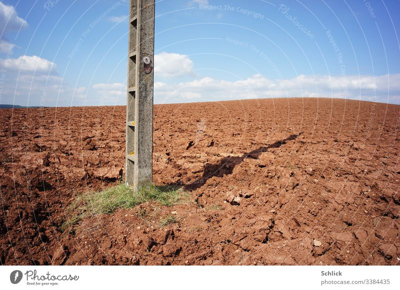 Field with bare earth and power pole with sign Danger of life under blue sky Monoculture Electricity pylon Danger of Life Text pesticides peril Earth