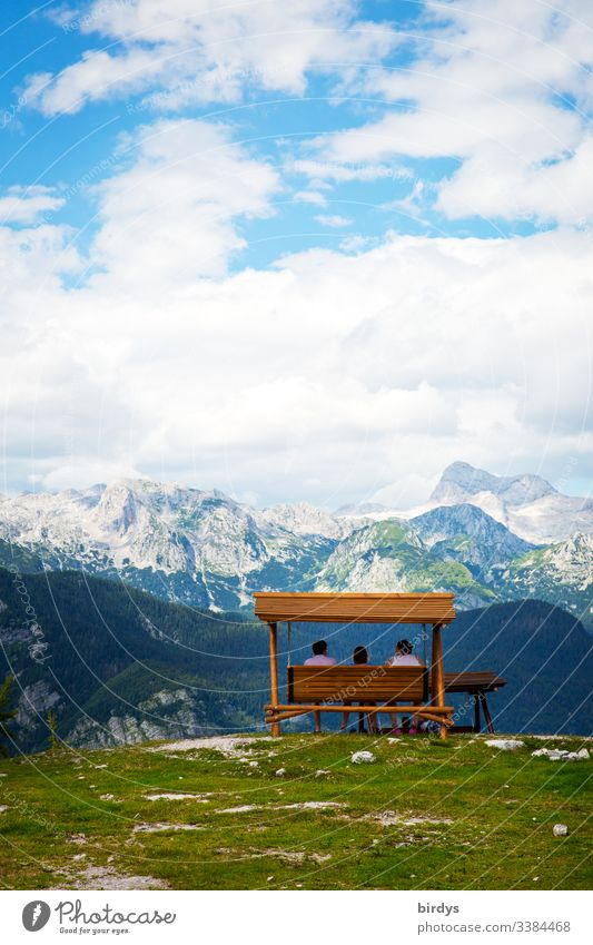 Tourists sit on a bench or swinging seat on the top of the mountain Vogel in Slovenia and marvel at the Alpine panorama in front of them . in the border triangle Slovenia - Austria and Italy. Ski area Vogel, Slovenia