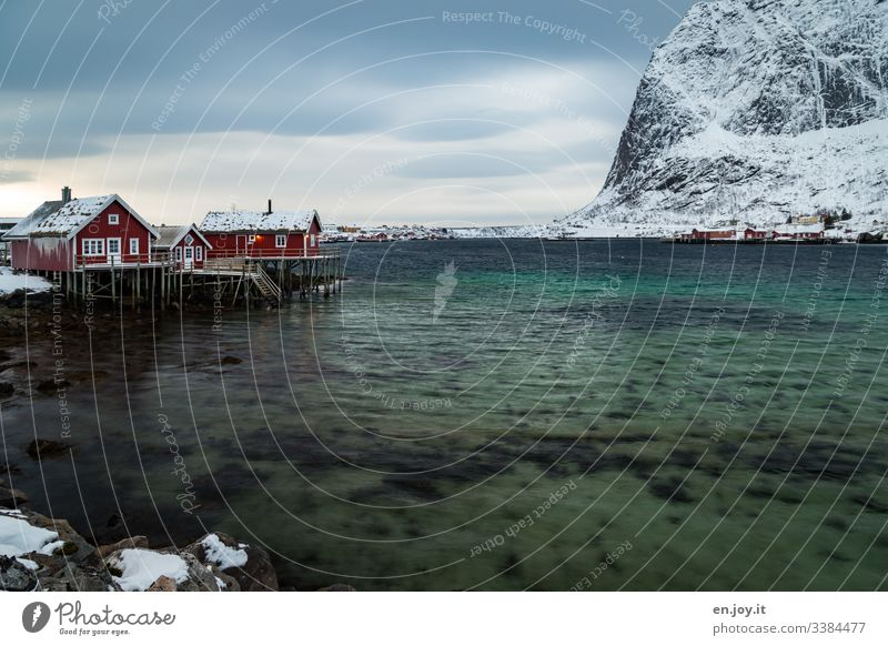Fishing huts by the fjord in front of snowy mountains Vacation & Travel Trip Winter Snow Winter vacation Environment Landscape Sky Clouds Wind Ice Frost