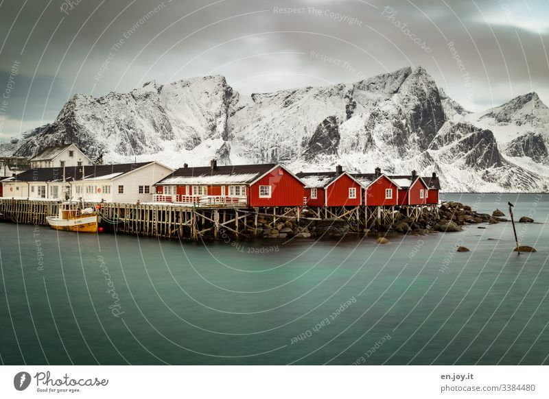 Fishing huts by the fjord in front of snowy mountains Vacation & Travel Trip Winter Snow Winter vacation Environment Landscape Sky Clouds Bad weather Wind Ice