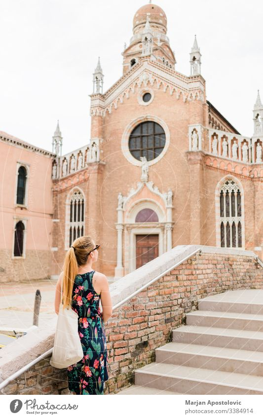 Young female traveler looking at the church in Venice, Italy ancient architecture attraction beautiful bridge building casual city cityscape culture day