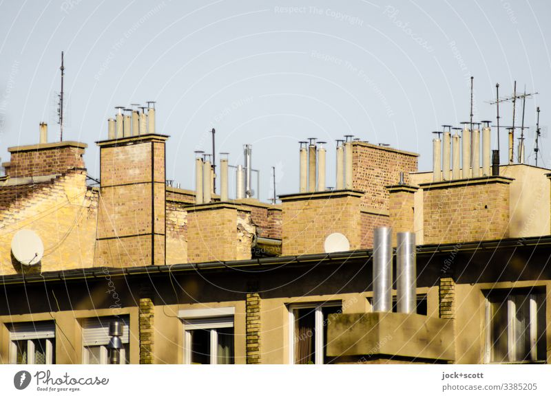 Collection of chimneys and a few antennas Side by side Roof Chimney Symmetry Nostalgia Climate Cloudless sky Window Above Sunlight Contrast Day