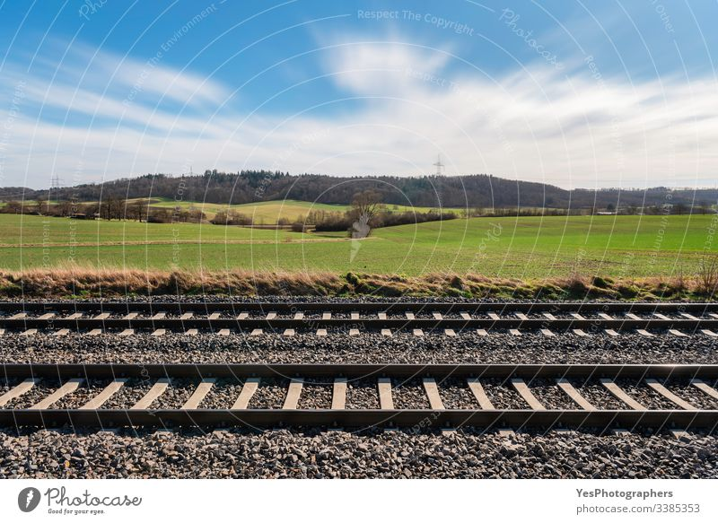 Railway tracks and sunny spring nature scenery. Railroad tracks Germany blue sky direction european railway forest german railroad gravel green fields hills