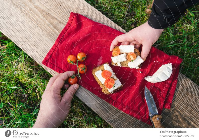 Serving food outdoor on grass. Picnic in sunlight on wood plank above view bread break camping cheese eating outdoor garden gourmet grabbing green grass hands
