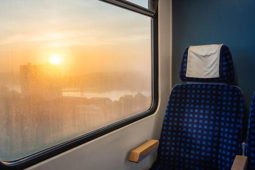 Train interior with chair and sunrise view on window. Train travel German train Germany blue chair carriage comfortable commute eco-friendly empty chair
