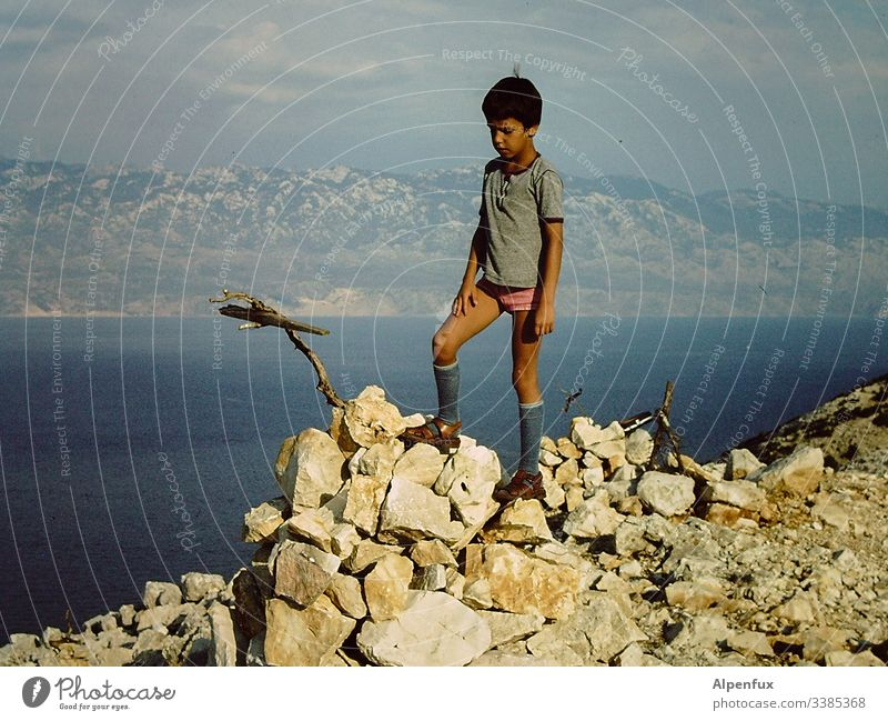 Young attractive child climbs a mountain with a stick in underpants Mountain Mountain range Mountain ridge Boy (child) Blue Hiking Mountaineering Nature