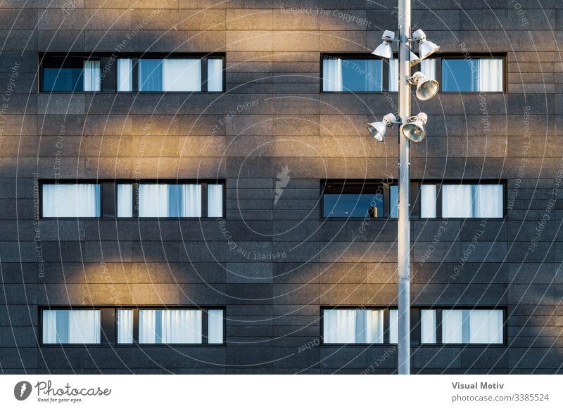 Streetlight and black facade of an urban building windows rows structure Architecture abstract building facade urban facade color exterior repetition no people