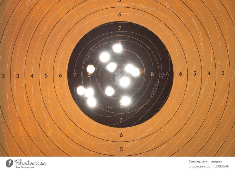 Close up of a shooting target with backlit bullet holes accuracy accuracy concept accurate aim aiming air army bullseye center close up competition competitive