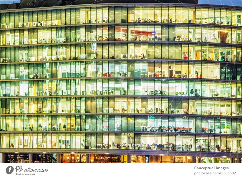 Exterior of an office at dusk, revealing the daily activity of the workers Ambition Architecture Building Building exterior Business Businesspeople Busy