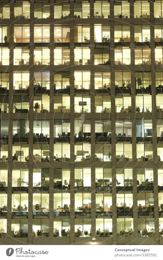 Exterior of an office at dusk, revealing the daily activity of the workers office block exterior overworked business people ambition architecture