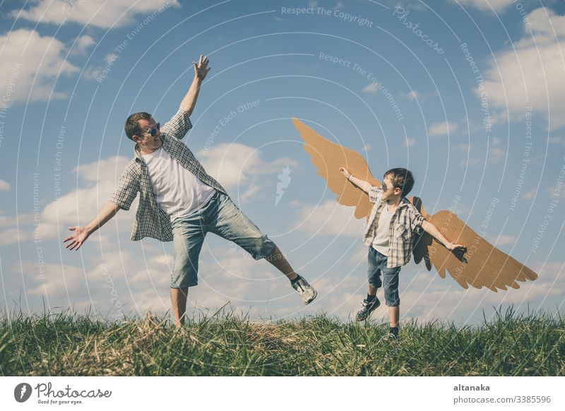 Father and son playing with cardboard toy wings father child outdoor family people parent lifestyle together fun day kid boy summer happiness dad man young joy