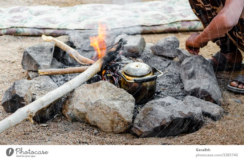 old kettle by the fire and people sitting next in Egypt Dahab South Sinai Bedouin tea Bedouins Middle East ashes bask beggar broken camouflage cook crisis