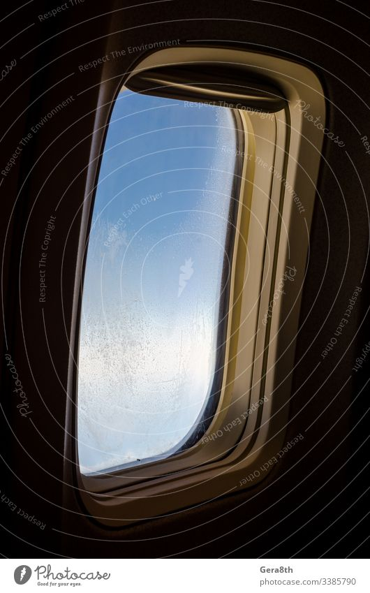 airplane window with frost on the glass isolated background black blue closeup flight hoarfrost ice pattern pattern on glass porthole sky technique travel