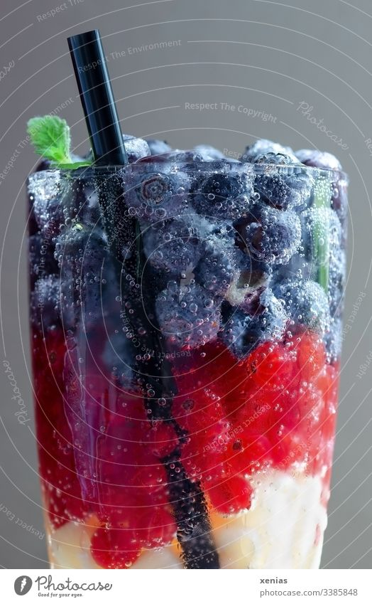 A glass of soft drink with berries and black straw Beverage Cold drink fruit Berries Vitamin-rich Fresh Vegetarian diet Blueberry Redcurrant Black Yellow
