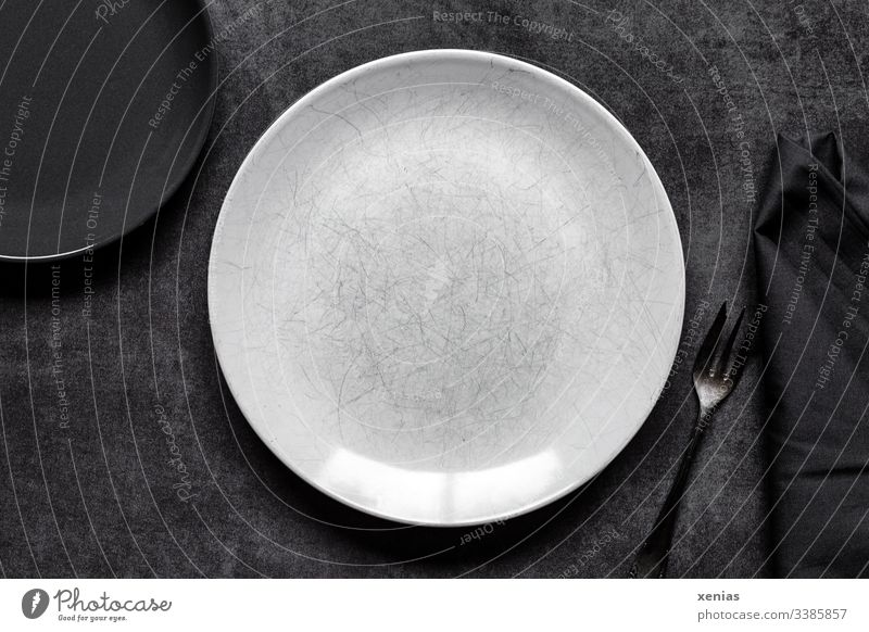 Light and dark plate with fork on grey background Plate Empty Food photograph Round White Interior shot Nutrition Fork Napkin Table Black scratched Eating