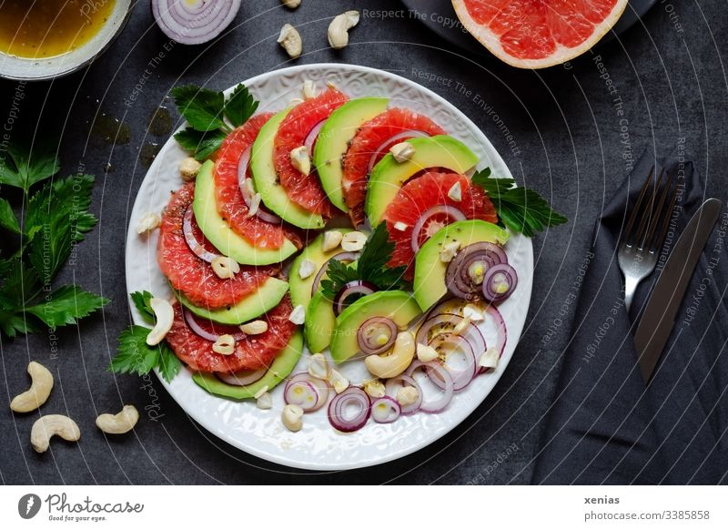 Salad with avocado, grapefruit, onions, cashew nuts and parsley served on a white plate with knife and fork in black napkin on a dark table Avocado Lettuce