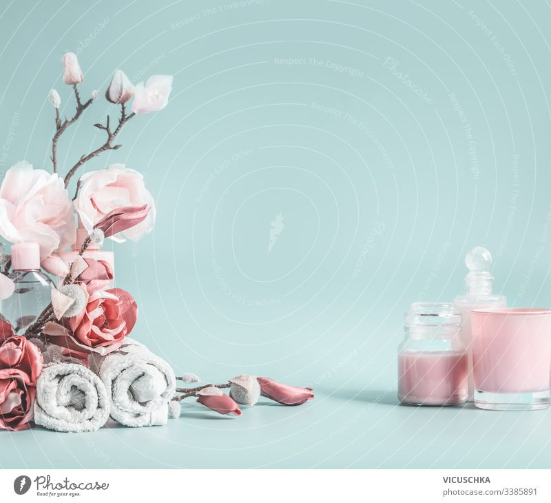 Beauty background with pastel pink flowers and cosmetic at pastel blue background beauty background health care desk modern cosmetics blank space table bottle