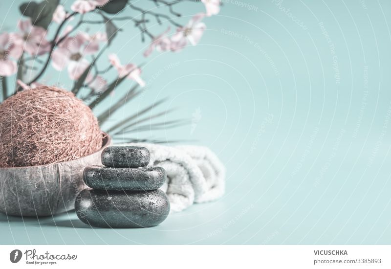 Zen stones with coco nut and towels at light blue background with flowers. Relaxing beauty day. Spa concept zen spa nobody relaxation closeup essentials