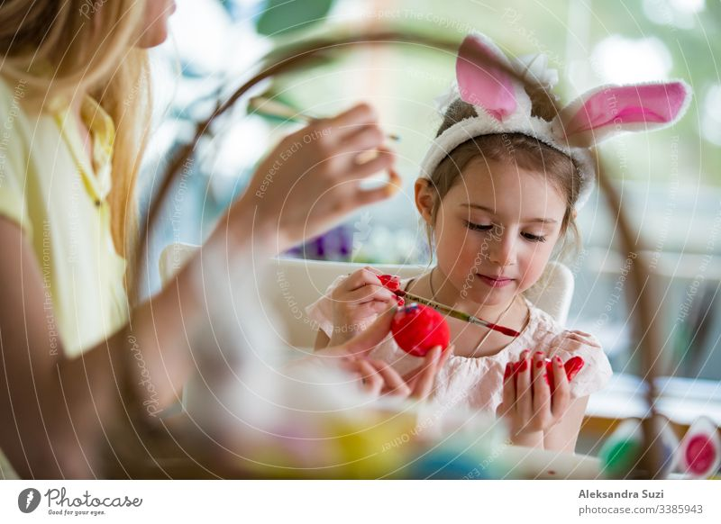 A mother and daughter celebrating Easter, painting eggs with brush. Happy family smiling and laughing. Cute little girl in bunny ears preparing the holiday.