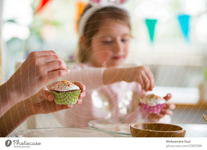Mother and daughter celebrating Easter, cooking cupcakes, covering with glaze. Happy family holiday. Cute little girl in bunny ears. baking candid celebration