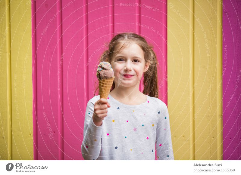 Cute little girl eating chocolate ice cream. Smiling and laughing. Colorful pink and yellow wall on background. Bright summer concept beautiful bright cafe