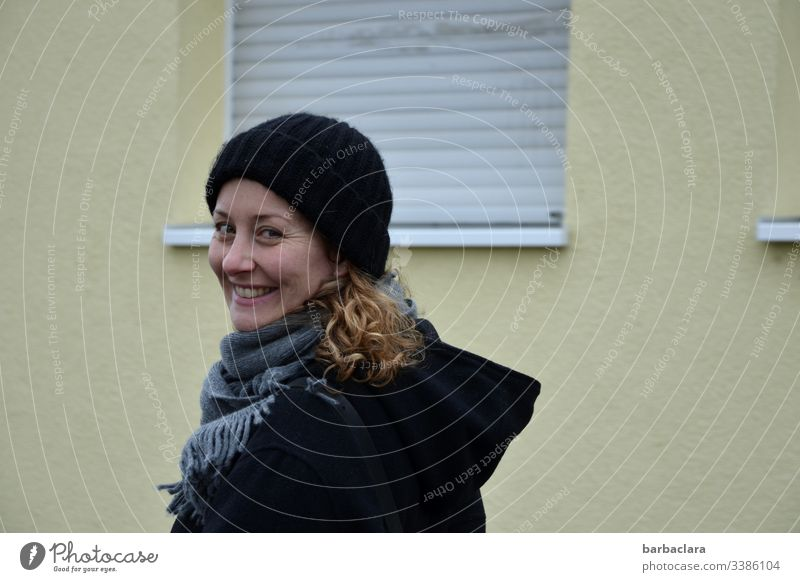 Life in front of a dreary wall roller shutter Woman Laughter House (Residential Structure) Curl cap Wall (building) Coat Black windowsill Gloomy Gray Autumnal