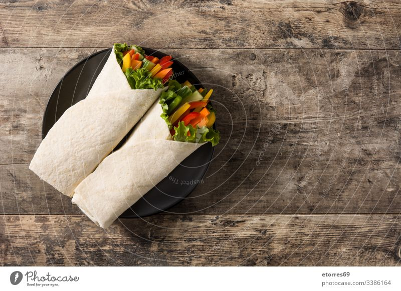 Vegetable tortilla wraps on wooden table. Top view. Copy space burrito carrot cucumber diet fajita food fresh green healthy lettuce mexican mix nutrition pepper
