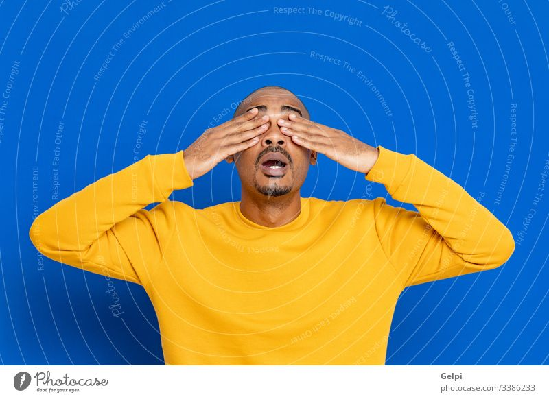 African guy with a yellow jersey black surprised exciting crazy happy emotion cover eyes blind closed blue adult people person african male american man