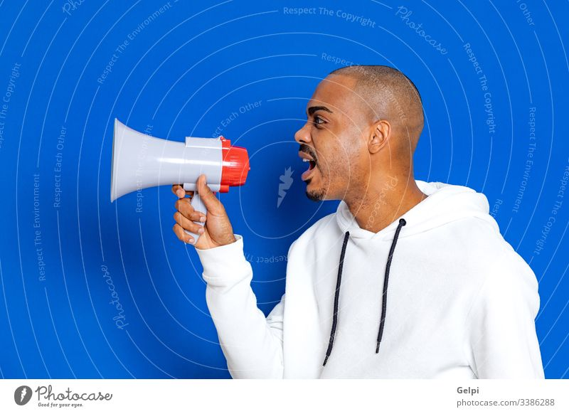 African guy wearing a white sweatshirt black blue megaphone loudspeaker yelling shout announce voice shouting communicate announcement ad advertisement adult